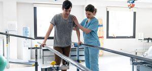Männlicher Patient bei der Physiotherapie geht mit Hilfe der Barren und des Therapeuten neben ihm