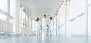 Drei Ärzte, die einen Flur im Krankenhaus hinuntergehen
