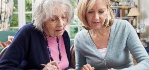 Nachbarin hilft älterer Frau ein Formular auszufüllen