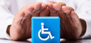 Ein Paar Hände schützt einen Würfel mit Rollstuhl-Symbol