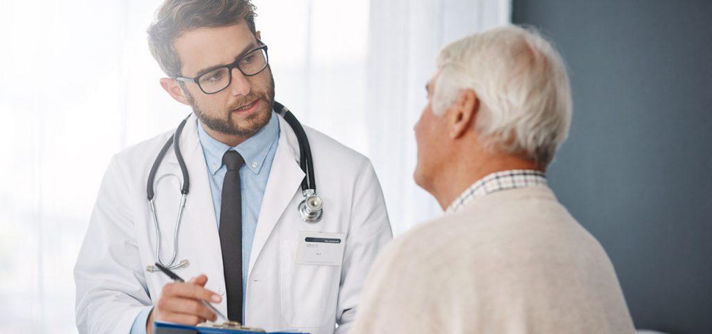 Ein Arzt im Gespräch mit einem älteren Patienten