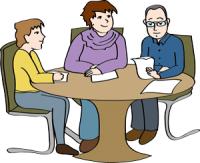 Drei Personen sitzen am Tisch.